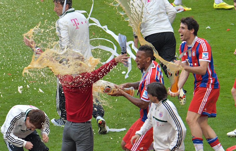 Bayern head coach Pep Guardiola of Spain, right, gets a shower of beer from Jerome Boateng, center, after Bayern Munich became the new Bundesliga champion after the German first division Bundesliga soccer match between FC Bayern Munich and VfB Stuttgart in the Allianz Arena in Munich, Germany, on Saturday, May 10. 2014. (AP Photo/Kerstin Joensson)