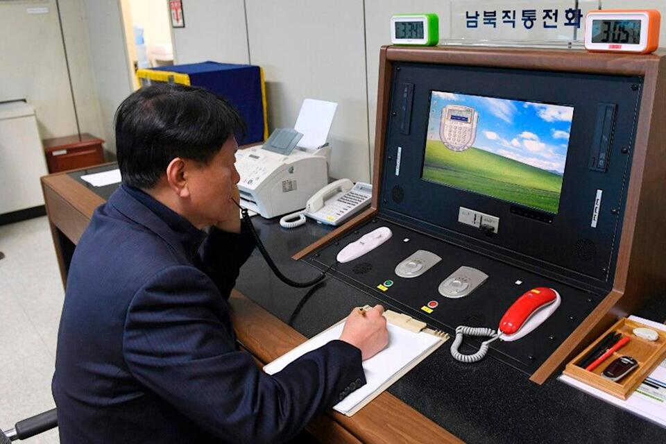 File: A South Korean government official communicates with a North Korean officer through hotline  (South Korea Unification Ministry)