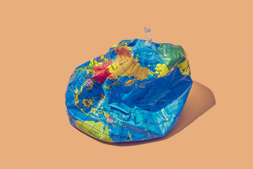An inflatable globe that has deflated to symbolise a deflated economy. The globe is bright blue and has an unplugged air vent. It's on a peach background.