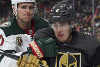 Minnesota Wild center Nick Bjugstad (27) and Vegas Golden Knights defenseman Zach Whitecloud (2) battle for the puck during the third period of Game 1 of a first-round NHL hockey playoff series Sunday, May 16, 2021, in Las Vegas. (AP Photo/David Becker)