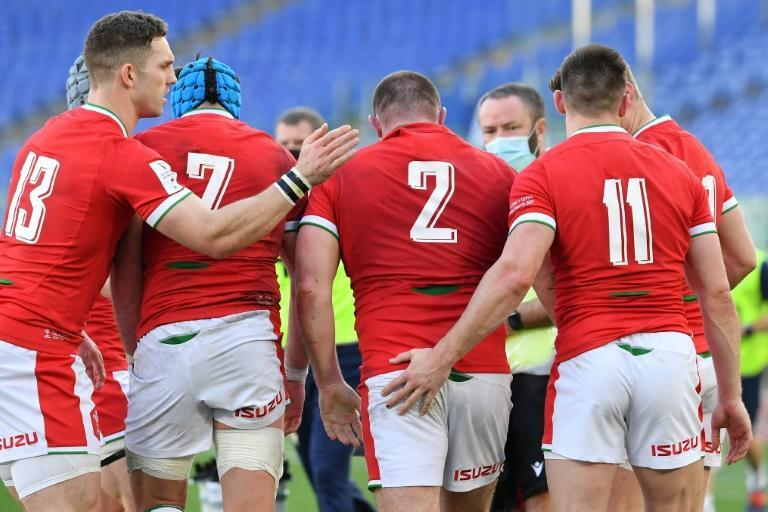 Wales' George North (L) and Joshua Adams (R) congratulate hooker Ken Owens after he scored a try against Italy.