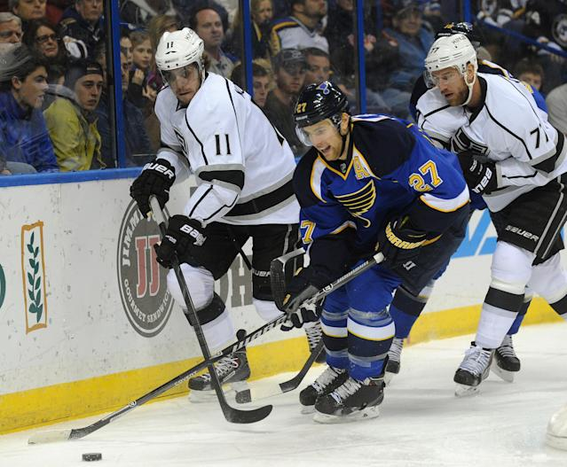 St. Louis Blues' Alex Pietrangelo (27) gets the puck past Los Angeles Kings' Anze Kopitar (11), of Slovenia, and Jeff Carter (77) during the first period of an NHL hockey game on Thursday, Jan. 2, 2014, in St. Louis. (AP Photo/Bill Boyce)