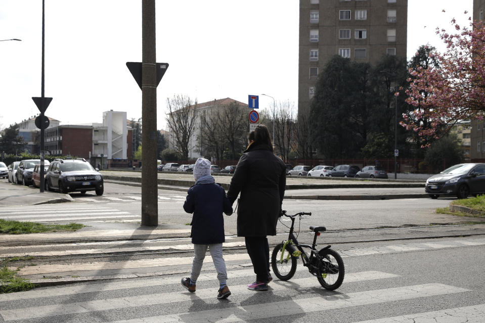 FILE - A woman walks with her daughter in Milan, Italy, Wednesday, April 1, 2020. Under Italy's more relaxed lockdown rules starting next week, people can visit family within the same region. But confusion abounds over how close the family connection needs to be. Does a second cousin qualify? A third? A sister-in-law's kids? When asked to clarify Prime Minister Conte muddied the water even more, saying those with relations of 'stable affection' would qualify. That left Italians wondering whether girlfriends or boyfriends would pass the test. (AP Photo/Luca Bruno)