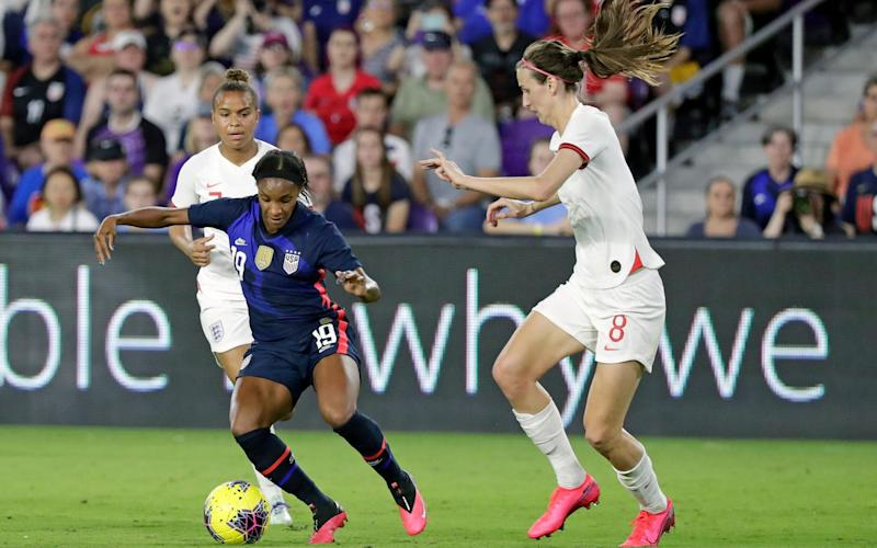 United States' Crystal Dunn, center, tries to maneuver past England's Jill Scott, right, during the first half of a She Believes Cup soccer match Thursday, March 5, 2020, in Orlando, Fla - AP