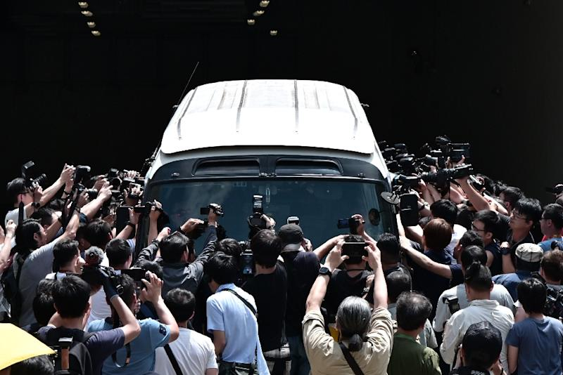 Members of the media surround a prison van carrying the four leaders sentenced to jail (AFP Photo/Anthony WALLACE)