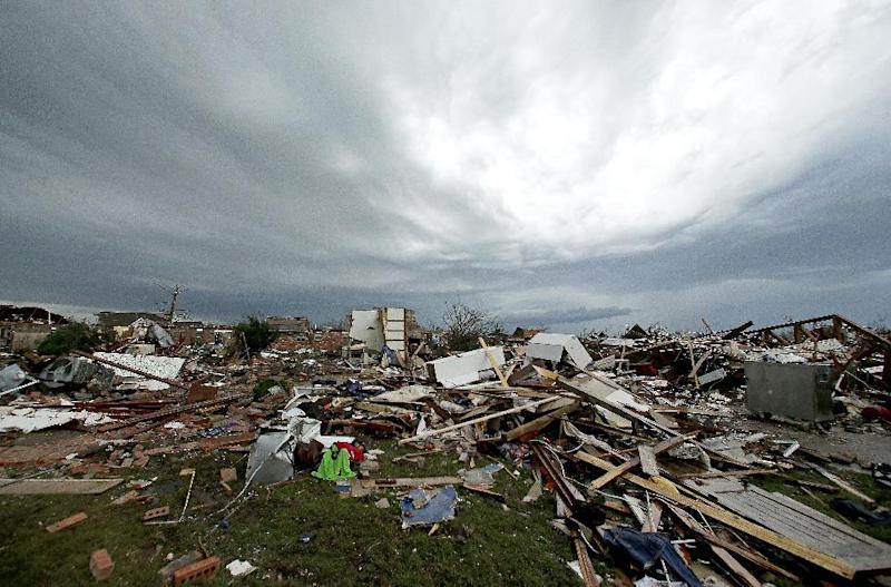 Storm clouds build in the distance beyond tornado-ravaged homes Tuesday, May 21, 2013, in Moore, Okla. A huge tornado roared through the Oklahoma City suburb Monday, flattening entire neighborhoods and destroying an elementary school with a direct blow as children and teachers huddled against winds. (AP Photo/Charlie Riedel)