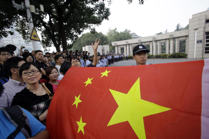 Protesters pull out a Chinese national flag in front of a local government office in Zhejiang province's Ningbo city, protesting the proposed expansion of a petrochemical factory Sunday, Oct. 28, 2012. Several hundred citizens of Ningbo gathered outside the offices of the municipal government and shouted for the city's mayor to come out and for the release of people they believed had been detained by police during demonstrations Saturday. (AP Photo/Ng Han Guan)