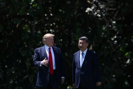 U.S. President Donald Trump and China's President Xi Jinping chat as they walk along the front patio of the Mar-a-Lago estate after a bilateral meeting in Palm Beach