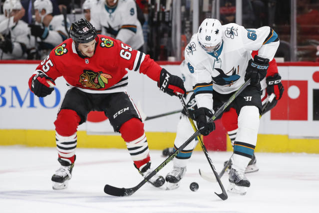 Chicago Blackhawks center Andrew Shaw, left, battles for the puck with San Jose Sharks center Melker Karlsson, right, during the first period of an NHL hockey game Thursday, Oct. 10, 2019, in Chicago. (AP Photo/Kamil Krzaczynski)