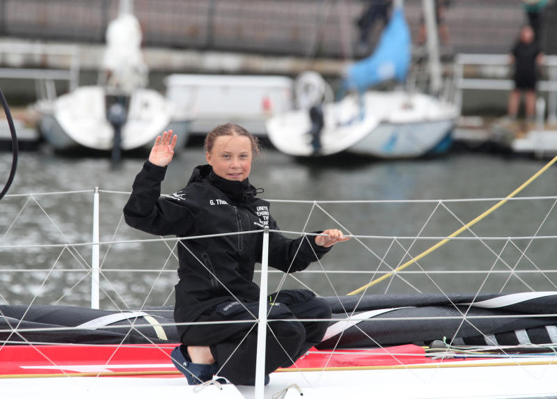 Greta Thunberg, a 16-year-old Swedish climate activist, waves after sailing in New York harbor aboard the Malizia II, Wednesday, Aug. 28, 2019. The zero-emissions yacht left Plymouth, England on Aug. 14. She is scheduled to address the United Nations Climate Action Summit on Sept. 23. (AP Photo/Mary Altaffer)