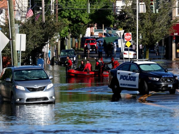 First responders pull residents in a boat following flooding in Mamaroneck, New York.