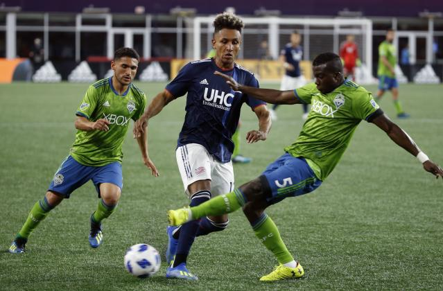 Seattle Sounders's Nouhou Tolo (5) and New England Revolution's Juan Agudelo, center, battle for the ball during the second half of an MLS soccer game in Foxborough, Mass., Saturday, July 7, 2018. (AP Photo/Michael Dwyer)