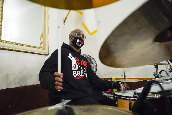 Terrence Floyd, brother of George Floyd, plays the drums with other artists during a recording session for an album of protest songs with the Rev. Kevin McCall Monday, Dec. 28, 2020, in New York. A full album of songs is set for release in May, one year after George Floyd's death at the hands of police in Minneapolis. Billed as the first album of its kind, the project follows a long history of racial justice messages and protest slogans crossing over into popular music and culture. (AP Photo/Frank Franklin II)