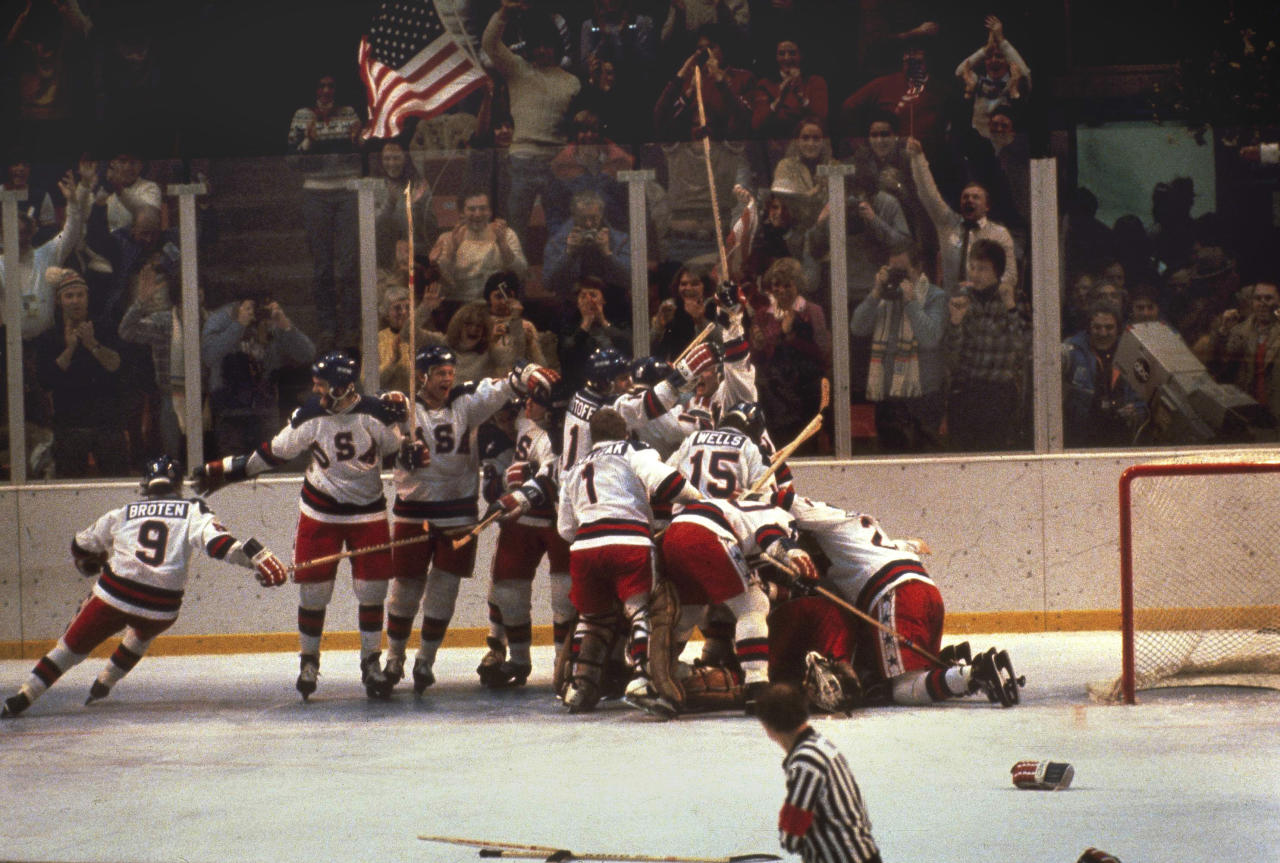 <p>Team USA piled onto goalie Jim Craig in celebration of their improbable 4-3 win over the Soviets to advance to the gold medal game. Fittingly, a fan in the stands behind them waved an American flag. </p>