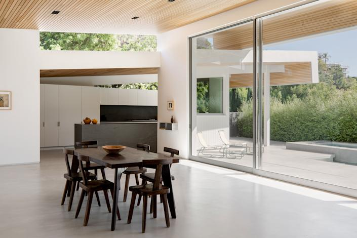 """<div class=""""caption""""> The interior of the home was completely gutted and reconfigured to be open and airy. The Benjamin Moore Super White paint on the walls adds an extra dose of brightness. </div>"""