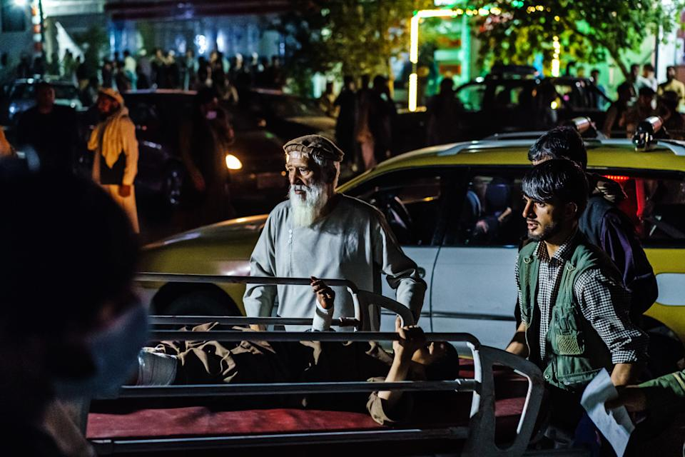 A wounded patient is brought by a taxi to the ER in Kabul after the bombings. Source: Getty