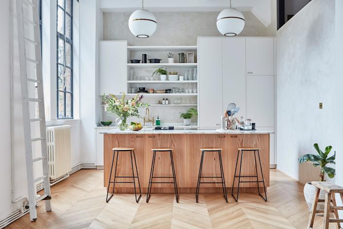 """<div class=""""caption""""> """"Anna needed as much worktop space as possible, so we designed a large island,"""" says George. """"We carefully aligned the position of the fridge, sink, and cooker, which makes moving around the space efficient and logical."""" </div>"""