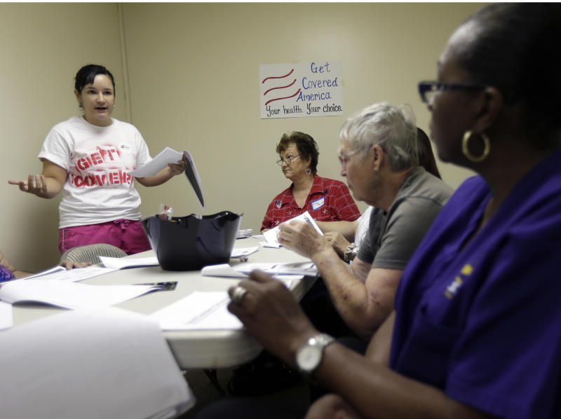 Alex Gonzalez, left, a volunteer with Enroll America, a private, non-profit organization running a grassroots campaign to encourage people to sign up for health care offered by the Affordable Care Act, trains volunteers who work the phones to inform residents of their health care options, Tuesday, Oct. 1, 2013, in Tampa, Fla. After months of build-up, Florida residents can start shopping for health insurance on government-run online marketplaces as the key component of the Affordable Care Act goes live. (AP Photo/Chris O'Meara)