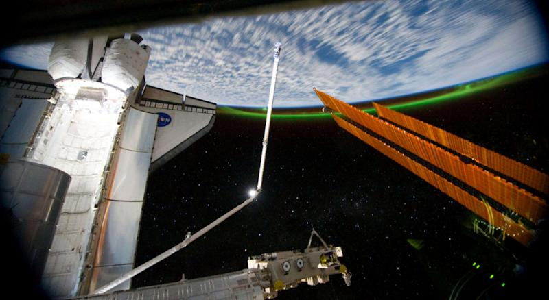 This panoramic view, photographed from the International Space Station, looking past the docked space shuttle Atlantis' cargo bay and part of the station including a solar array panel toward Earth, was taken on July 14 as the joint complex passed over the southern hemisphere. Aurora Australis or the Soutern Lights can be seen on Earth's horizon and a number of stars are visible also.