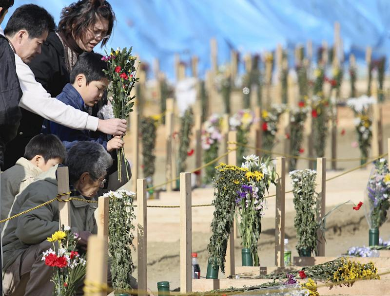 Survivors place flowers at the site where coffins of victims of the March 11 earthquake and tsunami were buried in Higashimatsushima, Miyagi Prefecture, Japan, Sunday, April 3, 2011. (AP Photo/Yomiuri Shimbun, Naoki Maeda) JAPAN OUT, MANDATORY CREDIT