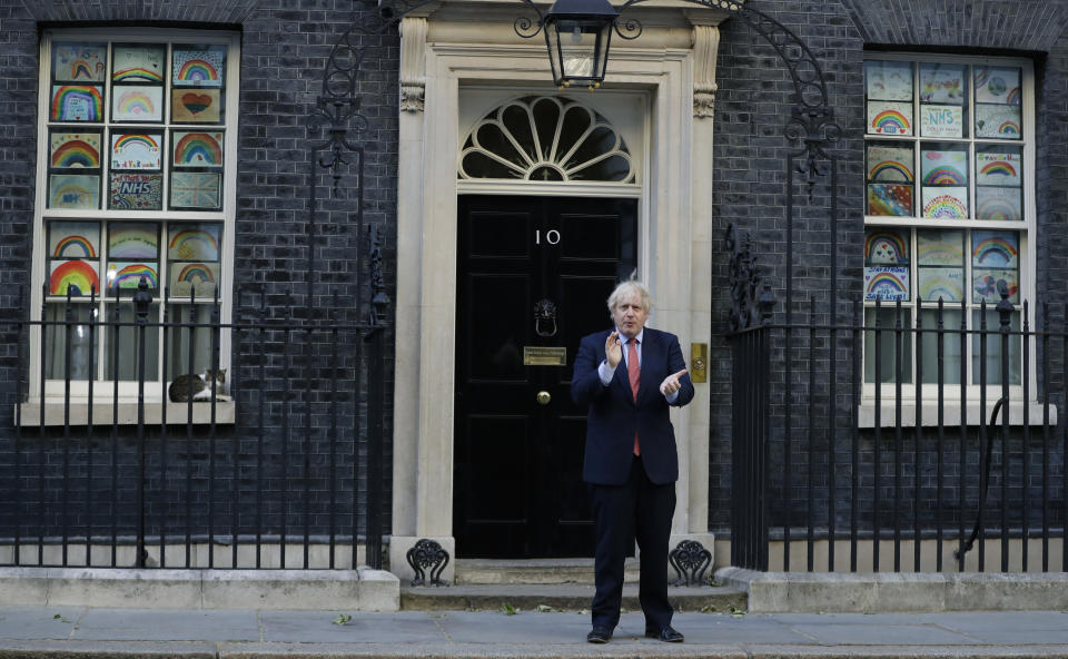 """Britain's Prime Minister Boris Johnson applauds on the doorstep of 10 Downing Street, during the weekly """"Clap for our Carers"""", in London, Thursday, May 28, 2020. The COVID-19 coronavirus pandemic has prompted a public display of appreciation for care workers. The applause takes place across Britain every Thursday at 8pm local time to show appreciation for healthcare workers, emergency services, armed services, delivery drivers, shop workers, teachers, waste collectors, manufacturers, postal workers, cleaners, vets, engineers and all those helping people with coronavirus and keeping the country functioning while most people stay at home in the lockdown. (AP Photo/Kirsty Wigglesworth)"""