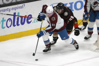 Colorado Avalanche forward Matt Calvert (11) controls the puck next to Anaheim Ducks forward Max Jones (49) during the second period of an NHL hockey game in Anaheim, Calif., Friday, Jan. 22, 2021. (AP Photo/Ringo H.W. Chiu)