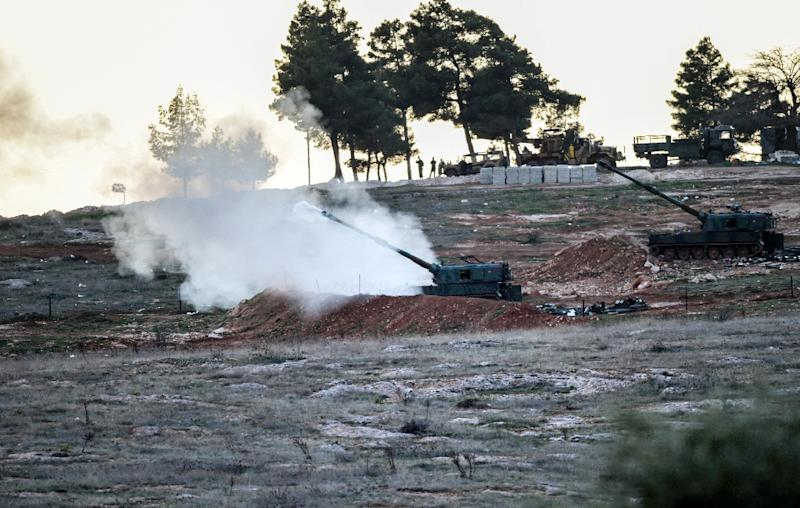 Tanks stationed at a Turkish army position near the Oncupinar crossing gate close to the Turkish border town of Kilis, fire towards the Syria border, on February 16, 2016 (AFP Photo/Bulent Kilic)