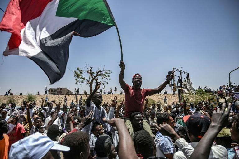 Sudanese protesters wave the national flag outside army headquarters in Khartoum in April 2019; demonstrations continued even after dictator Omar al-Bashir's fall, to force the military into sharing power