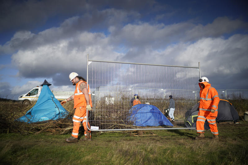 LEAMINGTON SPA, ENGLAND - JANUARY 28: HS2 workers carry fencing past a temporary camp to prevent a hedgerow being removed on the HS2 route near the village of Offchurch on January 28, 2020 in Leamington Spa, England. The Prime Minister is due to announce whether the HS2 rail project will go ahead within the next two weeks as costs for the project have more than doubled. (Photo by Christopher Furlong/Getty Images)