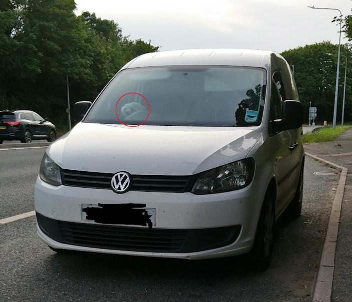 The van belonging to a man who was pulled over doing 90mph - with his dog (visible in the driver's seat, circled) on his lap, on the M20 in Kent. (SWNS)