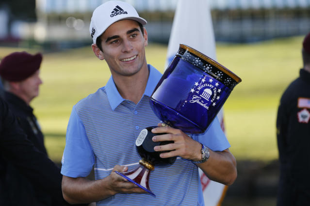 Joaquin Niemann, of Chile, holds the winners trophy as he celebrates winning the A Military Tribute at The Greenbrier golf tournament in White Sulphur Springs, W.Va., Sunday, Sept. 15, 2019. Niemann finished the tournament at 21-under-par. (AP Photo/Steve Helber)