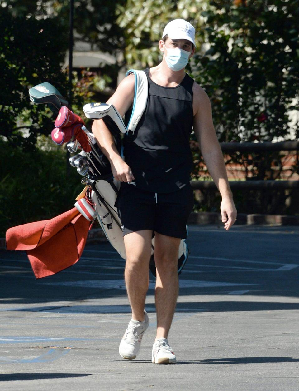 <p>Miles Teller carries his clubs as he heads to the golf course on Tuesday in L.A.</p>