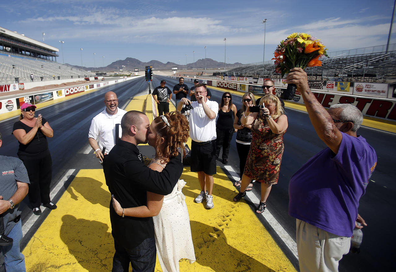 LAS VEGAS - OCTOBER 6:  The Las Vegas Wedding Wagon's the Rev. Andy Gonzalez (2nd L) officiates a wedding between Josh Davis and Martha Arrey of California as the Rev. James Cass takes pictures at the drag racing strip at the Las Vegas Motor Speedway on October 6, 2012 in Las Vegas, Nevada. For USD 99, ordained ministers will drive a van with an altar to any location in and around Las Vegas and perform a legal wedding, vow renewal or commitment ceremony in about 10 minutes. The fee includes wedding photos but not a marriage license. Couples can either get hitched at the Wedding Wagon's walk-up window or at iconic areas including the Welcome to Fabulous Las Vegas sign, the fountains at the Bellagio, the Hoover Dam and pedestrian bridges overlooking the Las Vegas Strip.  (Photo by Isaac Brekken/Getty Images)