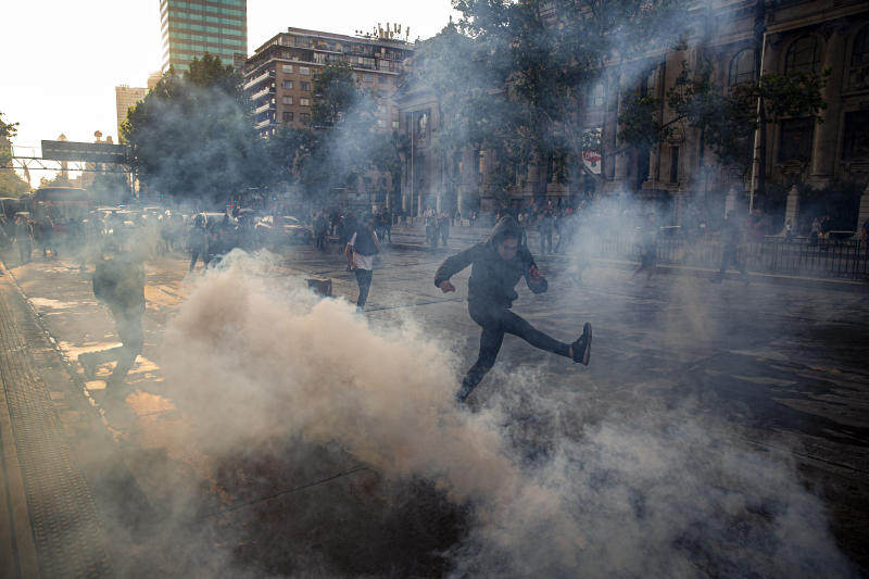 A protester kicks a tear gas canister launched by police near the Santa Lucia subway station during a protest against the rising cost of subway and bus fares, in Santiago, Friday, Oct. 18, 2019. (AP Photo/Esteban Felix)