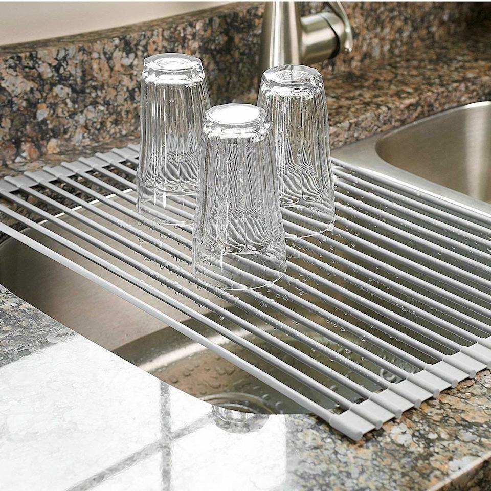 """Tiny apartment dwellers, rejoice! This is a major space saver and surprisingly multifunctional. It can also be used as a trivet mat on your countertop or simply as a way to turn your sink into some extra counter space when you're cooking. It's heat-resistant up to 400 degrees F and can be tossed in the dishwasher for easy cleaning.<br /><br /><strong>Promising review:</strong>""""It is incredibly versatile and a wonderful addition to our kitchen.<strong>So far I have used it for drying large items over the sink, filling a pot when the sink was already full, and as a counter trivet for a hot pan, and it performs beautifully in all these roles.</strong>The metal rods are strong and sturdy enough to hold heavy items, long enough to span our sink from multiple angles, and best of all, it rolls up for easy storage when not in use. All around a great kitchen tool, and I'll never be without one again."""" —<a href=""""https://www.amazon.com/dp/B00P8KHRIU?tag=huffpost-bfsyndication-20&ascsubtag=5833640%2C26%2C43%2Cd%2C0%2C0%2C0%2C962%3A1%3B901%3A2%3B900%3A2%3B974%3A3%3B975%3A2%3B982%3A2%2C16261651%2C0"""" target=""""_blank"""" rel=""""noopener noreferrer"""">T. Eicher<br /></a><br /><strong>Get it from Amazon for<a href=""""https://www.amazon.com/dp/B00P8KHRIU?tag=huffpost-bfsyndication-20&ascsubtag=5833640%2C26%2C43%2Cd%2C0%2C0%2C0%2C962%3A1%3B901%3A2%3B900%3A2%3B974%3A3%3B975%3A2%3B982%3A2%2C16261651%2C0"""" target=""""_blank"""" rel=""""noopener noreferrer"""">$24.98+</a>(available in two sizes).</strong>"""
