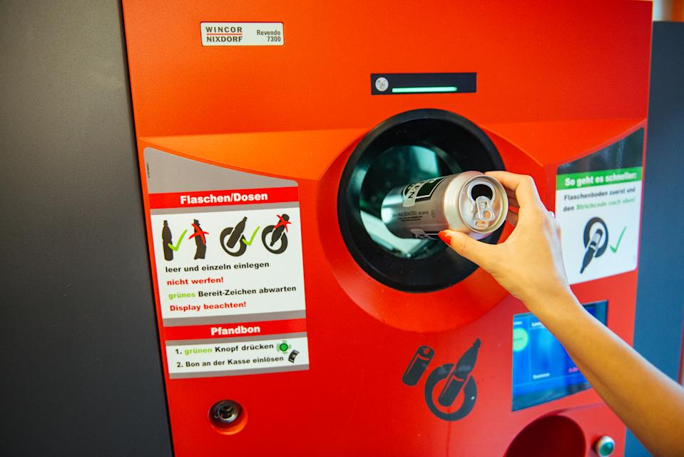 Berlin, Germany - August 31, 2015: Unrecognizable woman throwing empty beer can in recycling machine in order to receive deposit given while paying at the till. In Germany prices are formed on the principle that customar adds 0.08€ when buying drink in glass bottle, while 0.25€ should be added on the beverage price if it is packed in can or plastic bottle. By recycling later on, you receive coupon with that amount which is cashable at the till in any store.