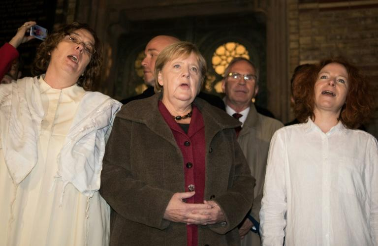German Chancellor Angela Merkel sings with members of the Jewish community at a vigil outside Berlin's main synagogue