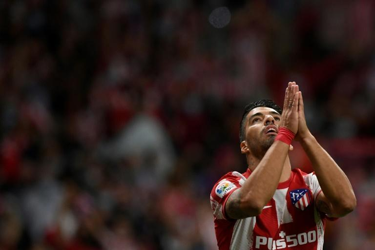 Atletico Madrid's Luis Suarez holds back from celebrating after scoring against his former club Barcelona on Saturday. (AFP/OSCAR DEL POZO)