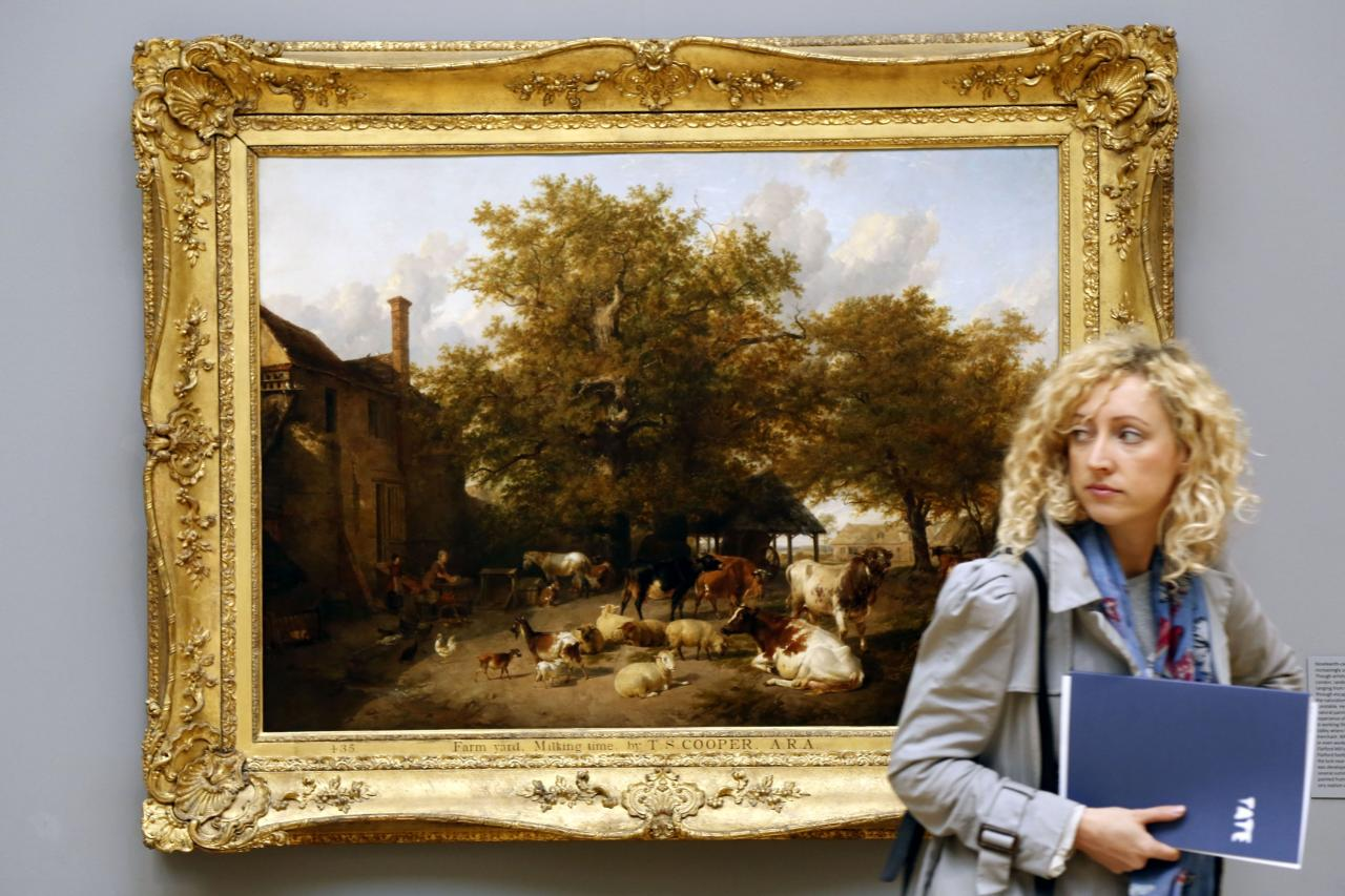 LONDON, UNITED KINGDOM - MAY 13: A woman walks past Farm Yard Milking Time by T.S Cooper on display at the Walk through British Art exhibition at Tate Britain on May 13, 2013 in London, England. Visitors will experience a completely new presentation of the world's greatest collection of British art, the national collection of British art will be displayed in a continuous and purely chronological display from the 1500s to the present day. (Photo by Warrick Page/Getty Images)