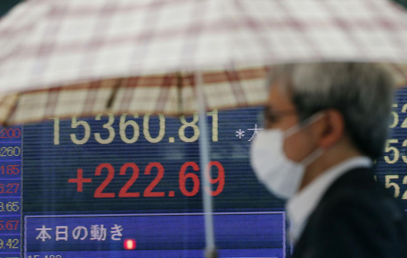 A man under an umbrella walks past an electronic stock board of a securities firm in Tokyo Monday, May 20, 2013. Japan's Nikkei 225 index jumped 1.4 percent to 15,352.84 as evidence of a steady economic recovery in the U.S. helped push Asian stock markets higher Monday. (AP Photo/Koji Sasahara)