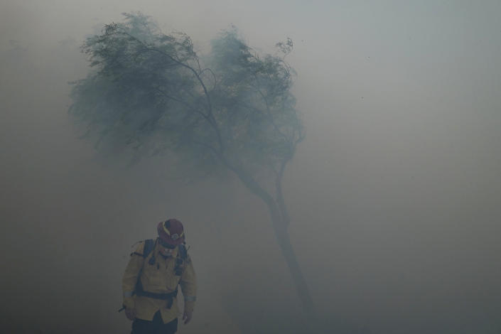 A firefighter braves gusty winds as heavy smoke from the Silverado Fire fills the air, Monday, Oct. 26, 2020, in Irvine, Calif. A fast-moving wildfire forced evacuation orders for 60,000 people in Southern California on Monday as powerful winds across the state prompted power to be cut to hundreds of thousands to prevent utility equipment from sparking new blazes. (AP Photo/Jae C. Hong)