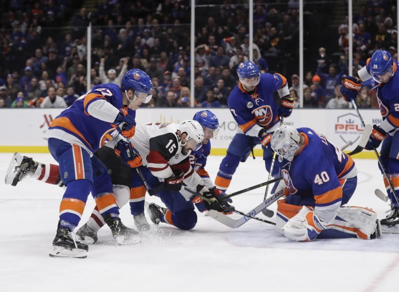 New York Islanders goaltender Robin Lehner (40) stops a shot on goal by Arizona Coyotes' Brad Richardson (15) as Islanders' Anders Lee (27) defends during the third period of an NHL hockey game Sunday, March 24, 2019, in Uniondale, N.Y. (AP Photo/Frank Franklin II)