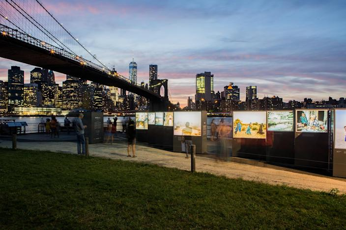 """<p>People view some of the 68 large-scale photographs on exhibition on the East River waterfront by Mustafah Abdulaziz, exploring the global water crisis for his long-term photographic project """"Water, """" on Sept. 21, 2016. (Alex Welsh) </p>"""