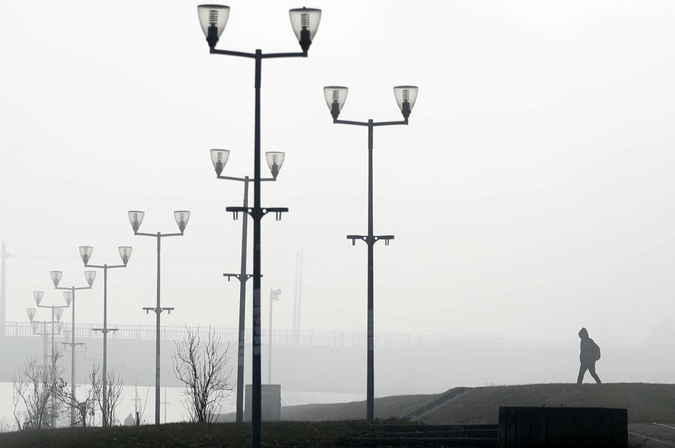 A man walks on the bank of Sava river in Belgrade, Serbia, Wednesday, Jan. 15, 2020. Serbia's government on Wednesday called an emergency meeting, as many cities throughout the Balkans have been hit by dangerous levels of air pollution in recent days, prompting residents' anger and government warnings to stay indoors and avoid physical activity. (AP Photo/Darko Vojinovic)