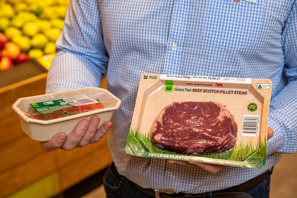 Woolworths worker holds tomato and meat tray.