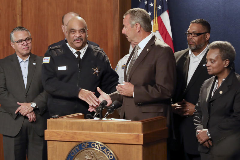 Former Los Angeles police Chief Charlie Beck, center, shakes hands with outgoing Superintendent Eddie Johnson, second from left, after he was named Chicago's interim police superintendent,  Friday, Nov. 8, 2019 in Chicago. Chicago Mayor Lori Lightfoot, right, made the announcement a day after Johnson said he would retire after more than three years as the city's police chief and more than 30 years with the department. (AP Photo/Teresa Crawford)