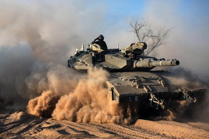 An Israeli soldier gestures on a Merkava tank, as part of the Israeli army deployment near Israel's border with the Gaza Strip on July 20, 2014 (AFP Photo/Menahem Kahana)