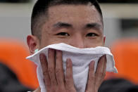 Shiyan Gao, from China, wipes away sweat during practice for the 3-on-3 basketball competition at the 2020 Summer Olympics, Wednesday, July 21, 2021, at the Aomi Urban Sports Park in Tokyo. (AP Photo/Charlie Riedel)