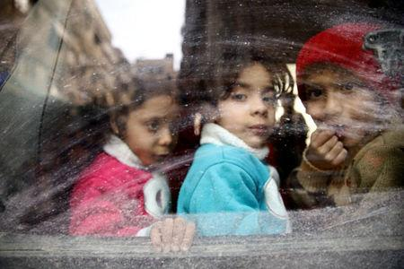 Children look through a bus window during evacuation from the besieged town of Douma, Eastern Ghouta, in Damascus, Syria March 13, 2018. REUTERS/Bassam Khabieh