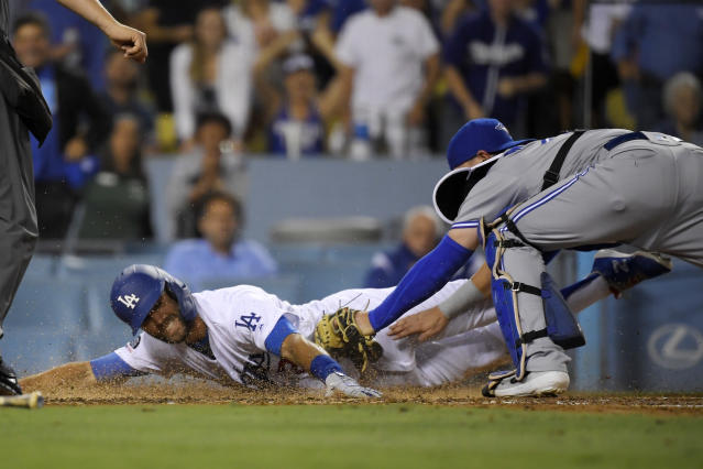 Los Angeles Dodgers' Chris Taylor, left, is tagged out by Toronto Blue Jays catcher Reese McGuire while trying for an inside-the-park home run during the fourth inning of a baseball game Wednesday, Aug. 21, 2019, in Los Angeles. (AP Photo/Mark J. Terrill)